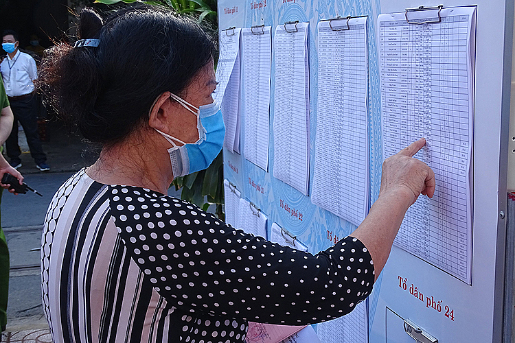 A woman reads up on info about candidates at a polling station in Phu Nhuan District.Nguyen Trong Trai, 64, said its already been his 10th time to go voting, but this years different due to the ongoing Covid-19 pandemic. People used to get long lines and theres excitement in the air before. But due to the Covid-19 and the mask wearing and social distancing, its a lot quieter now.Trai said would vote for young candidates who are highly skilled and experienced. Young people have new ways of thinking and doing things to develop the economy and take care of peoples lives.