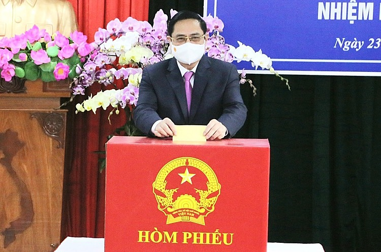 Prime Minister Pham Minh Chinh casts his votes into a ballot box at a polling station in Ninh Kieu District, Cai Khe Ward.