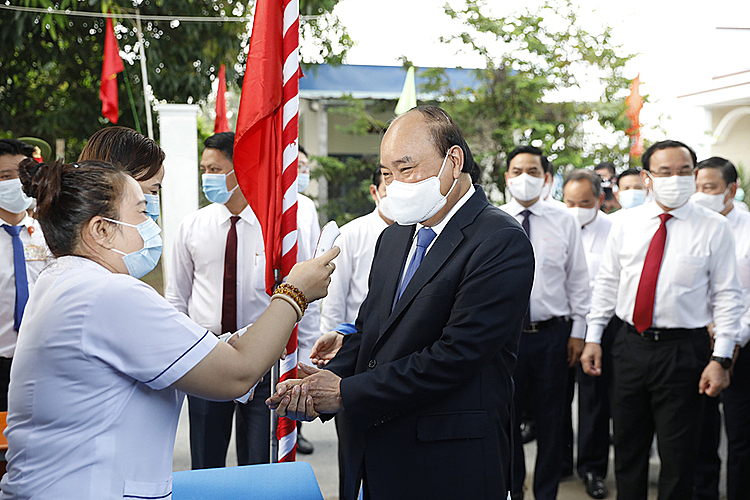 President Nguyen Xuan Phuc has his body temperature checked and his hands disinfected prior to the voting process in Cu Chi Town.