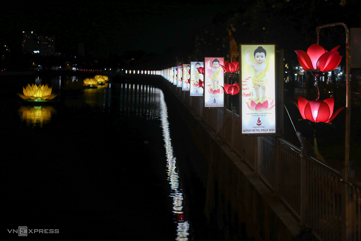 Paintings of the baby Buddha is hung by the canal along with more lanterns in lotus shape.