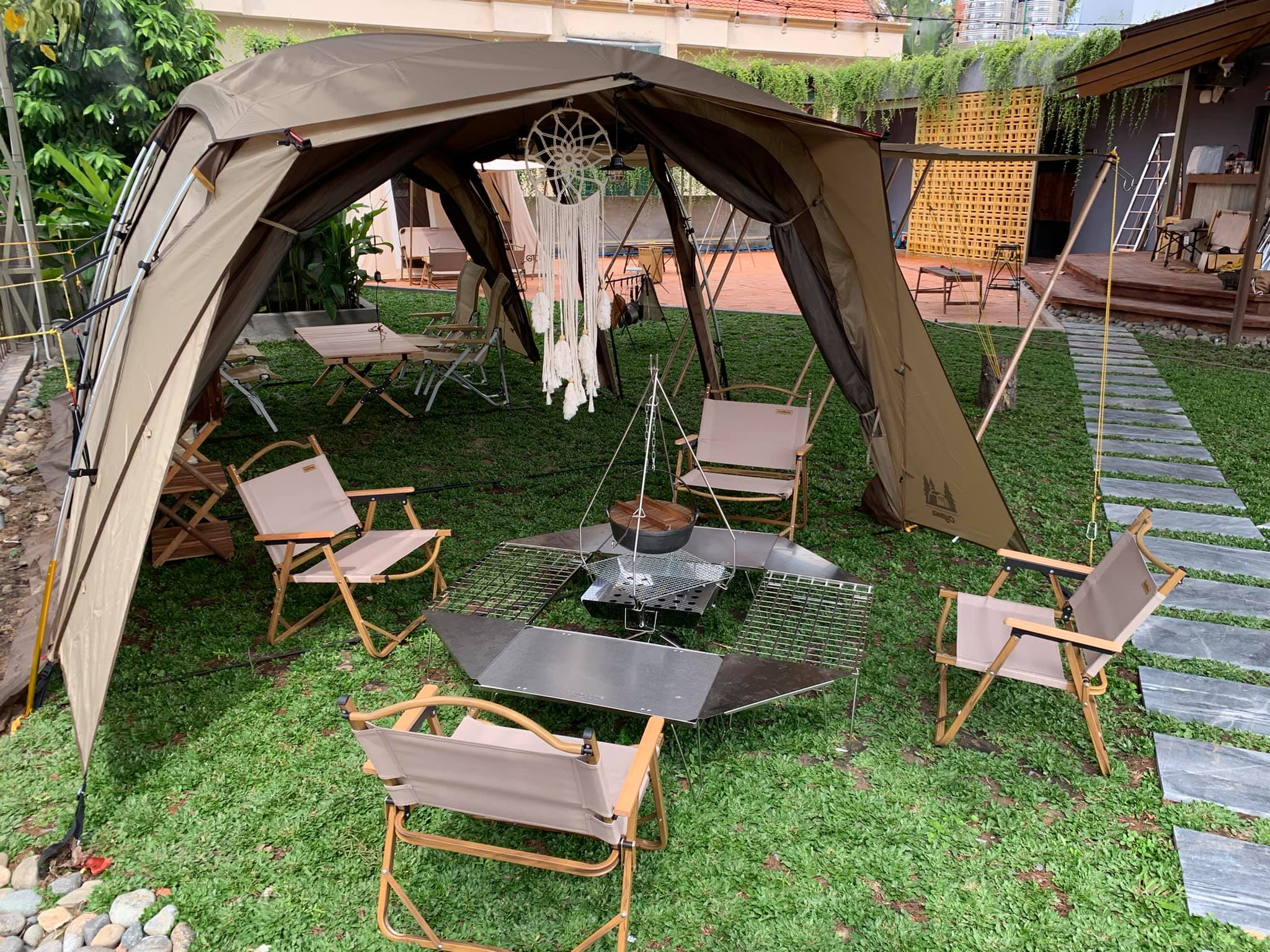 The cafe is equipped with unique design from professional camping equipment such as tents, lamps, pans, pots, kettles or grills amid the green space.