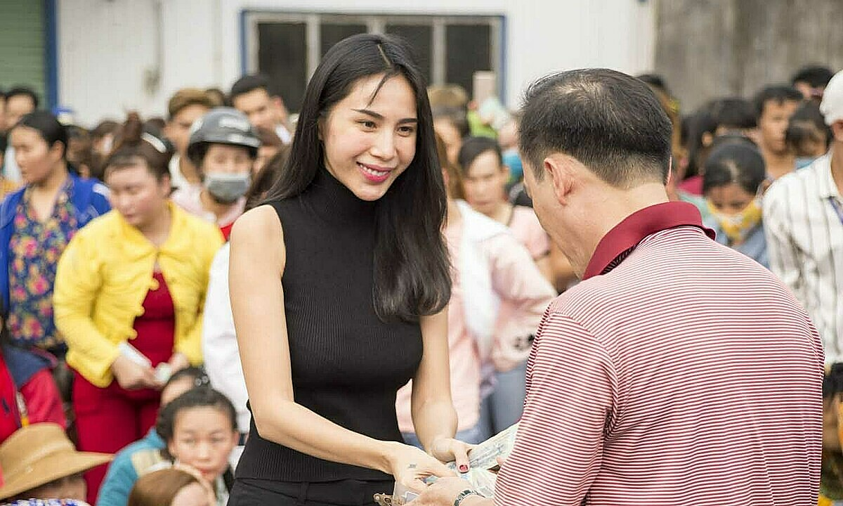 Pop singer Thuy Tien handles cash to a man in the central region. Photo courtesy of Thuy Tien.