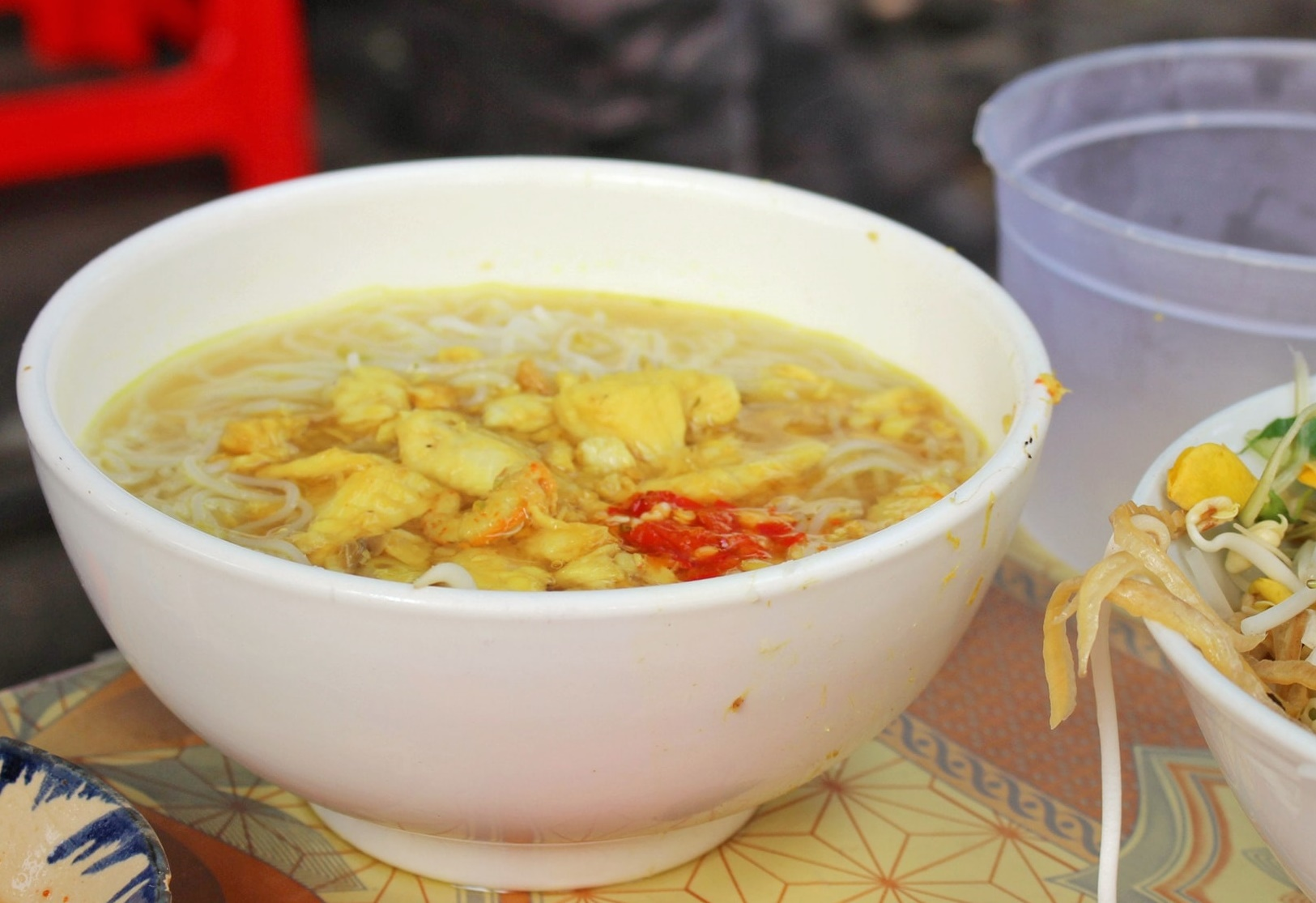 The success of the dish lies in the sweet broth that is made from fermented carp, shrimp paste, livestock bones and other ingredients such as auttum crosscus and crushed turmeric. Dont forget to enjoy the dish with some vegetables such as water spinach, banana flower, bean sprouts, dien dien or sesban leaves, accopanied with a cup of tamarind sauce. A bolw of fish noodle soup at Ms.Les stall costs VND15,000 ($0.65).