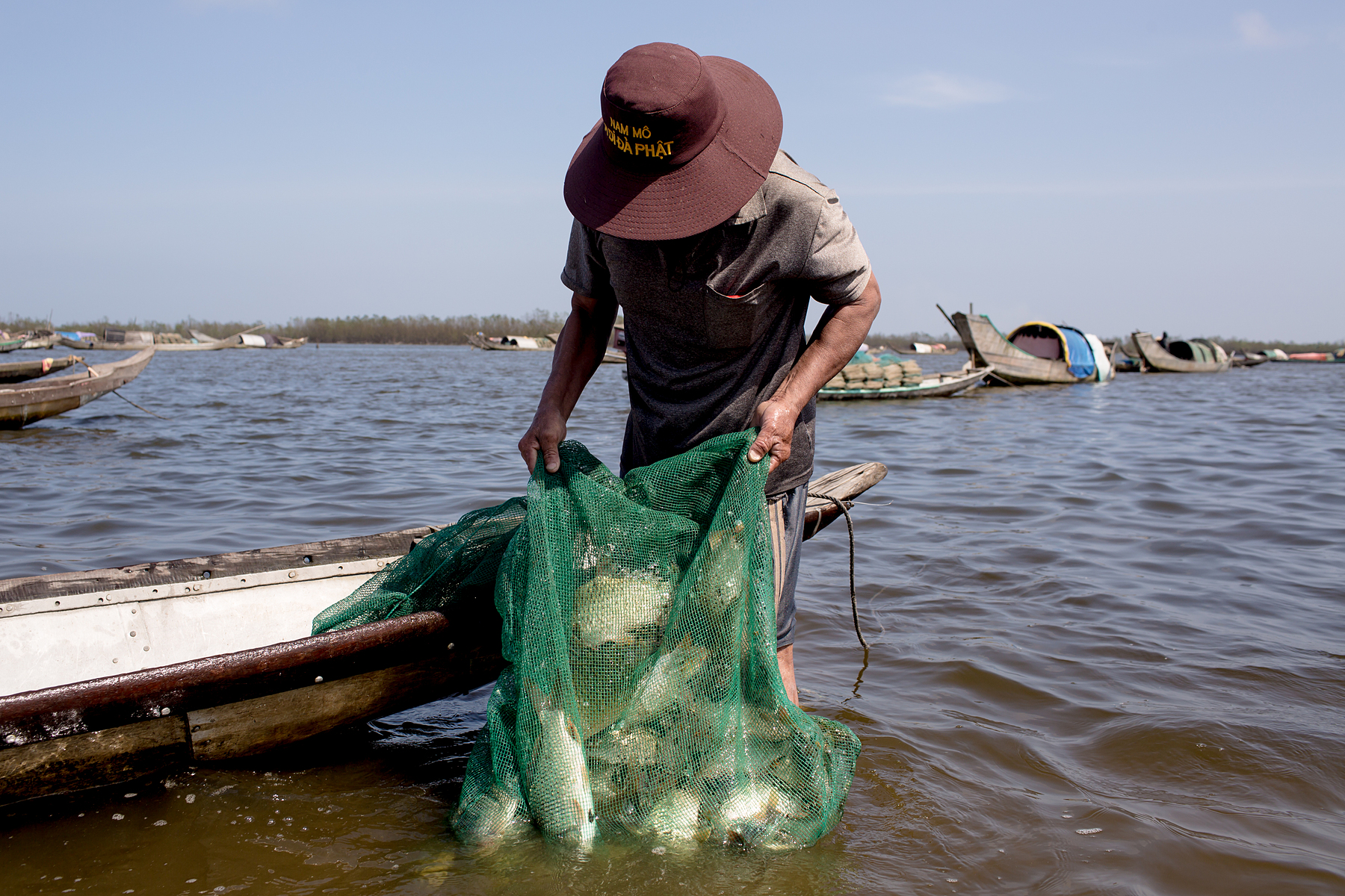 A fisherman wearing a wide-brimmed hat stands calf-deep in the water next to his boat and looks down at his fishing net.