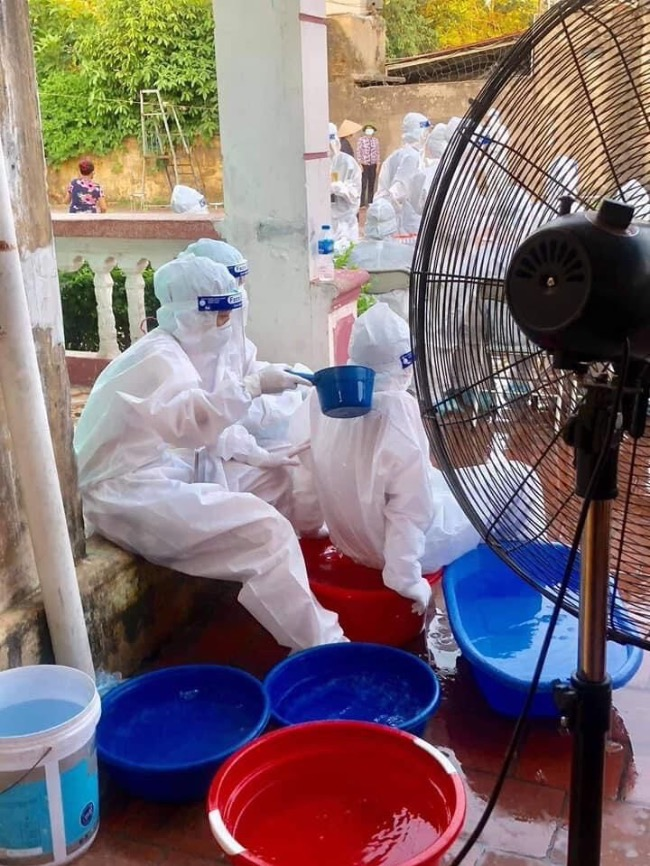Health workers pour water on their bodies to keep cool. Photo courtesy of Mai Hoang Hai.