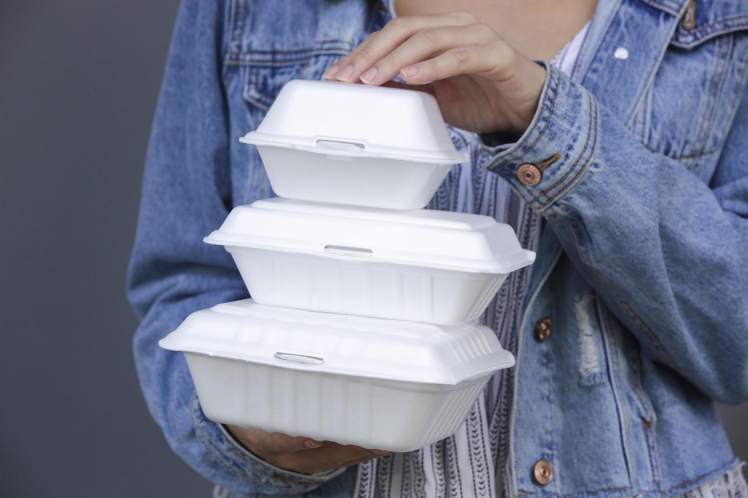 A woman holds takeaway foam boxes. Photo by Shutterstock/triocean