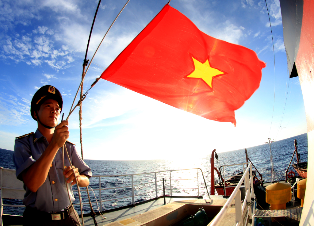 Vietnams national flag is raised at a ceremony in the Hoang Sa Islands waters in June 2014. Photo by Le Thanh Tung.