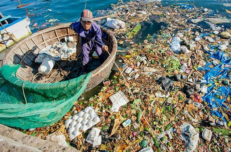 A man stands on a coracle surrouded by plastic and other waste in Ly Son Island, central Vietnam, 2019. Photo by VnExpress/Thanh Nguyen.