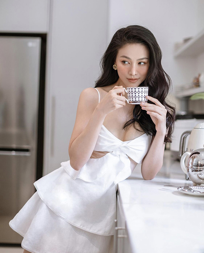 Wearing elegant dresses of many Vietnamese fashion brands is Miss Earth 2018 Phuong Khanhs favorite style this summer. The beauty queen poses for a photo wearing a spaghetti strap cut-out dress in her home kitchen.