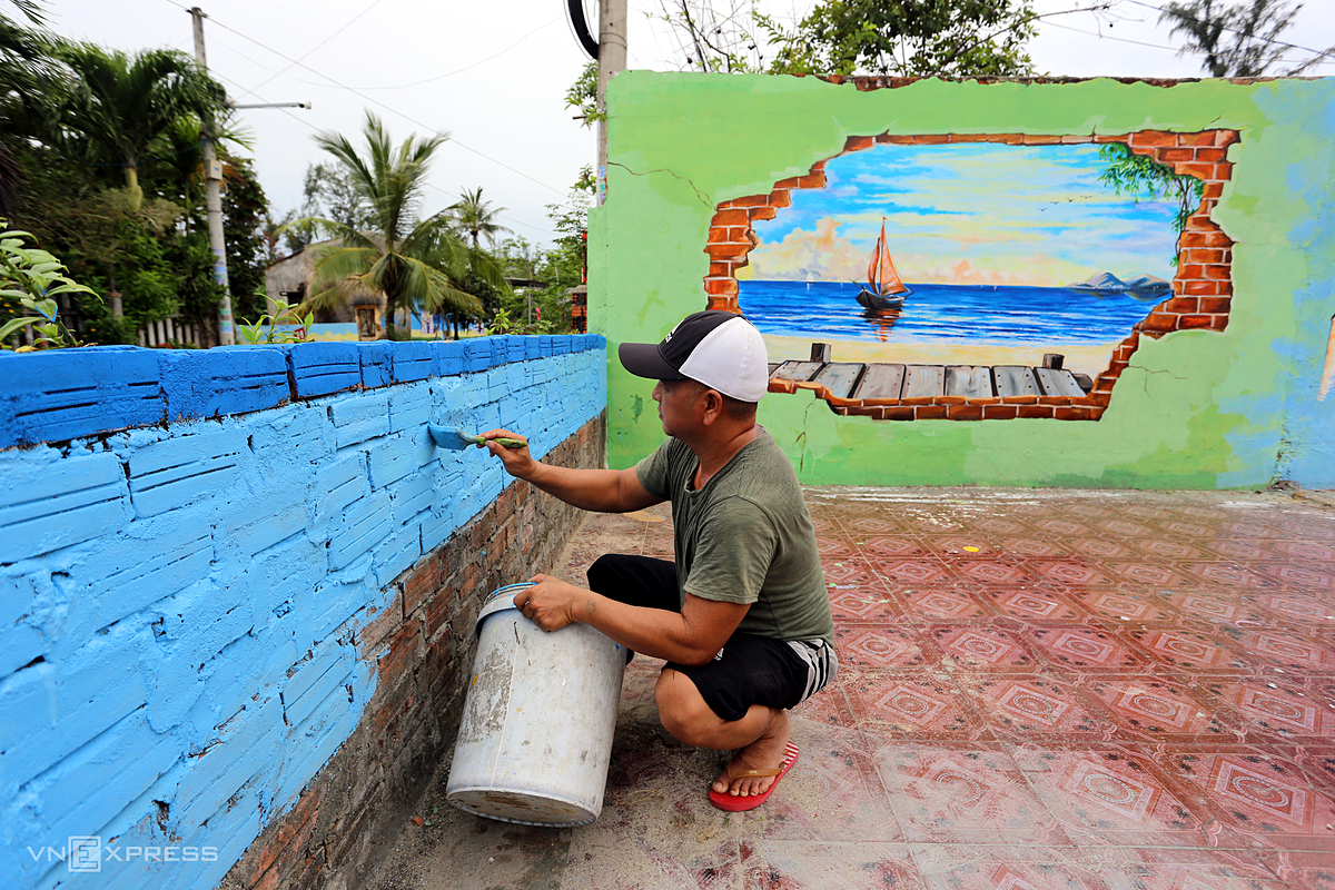 Tran Khanh Binh, a villager, decorates his home.   Before the pandemic broke out, a large number of visitors flocked to visit the mural village but there are few at this time, he said.