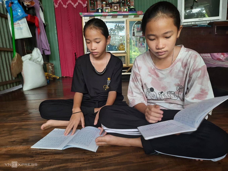 Twin sisters Kim Ngan and Kim Ha studying at home. Photo by VnExpress/Ngoc Tai.