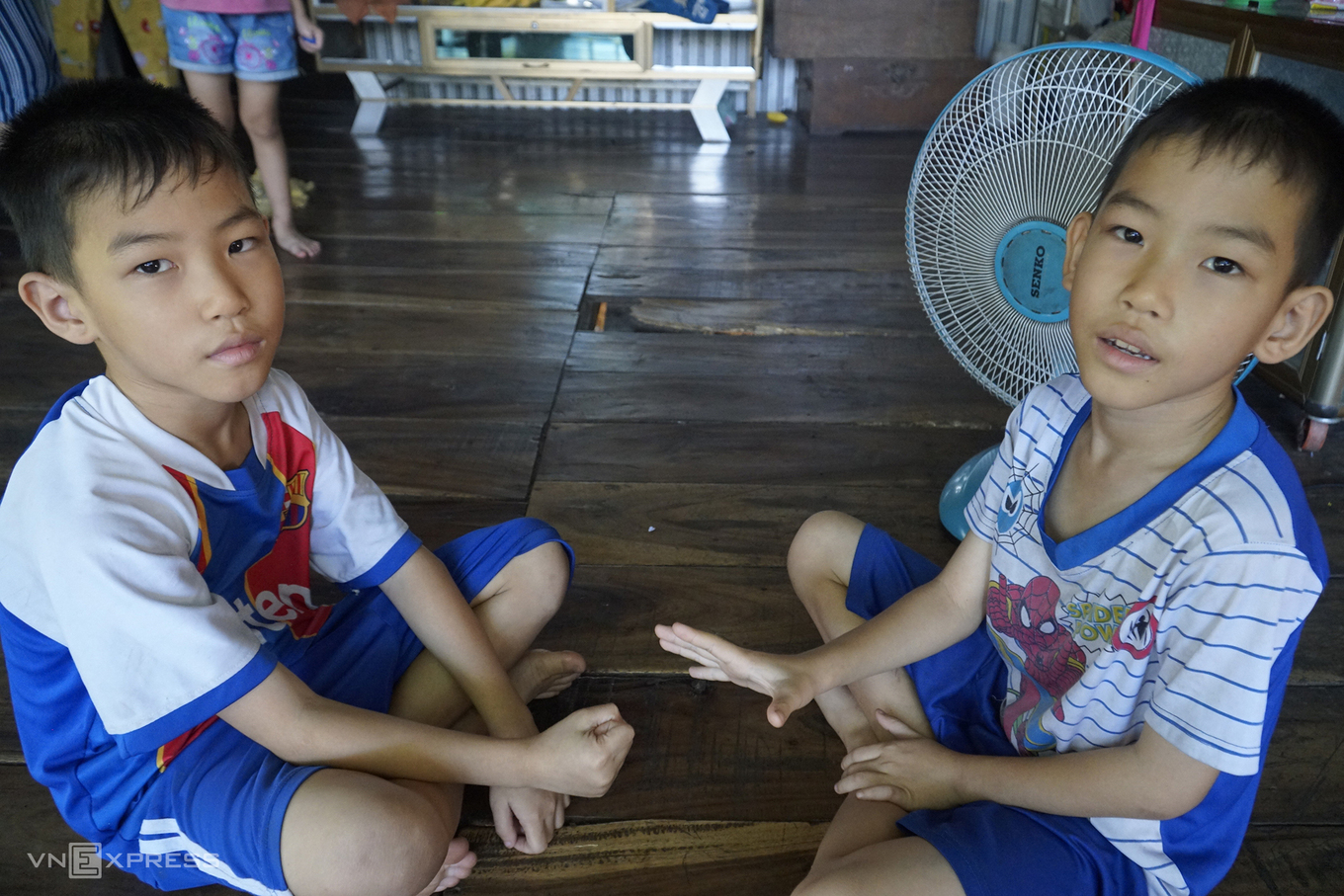 Two twin boys, sons of Cao Thi Diem, play games with each other. Photo by VnExpress/Ngoc Tai.