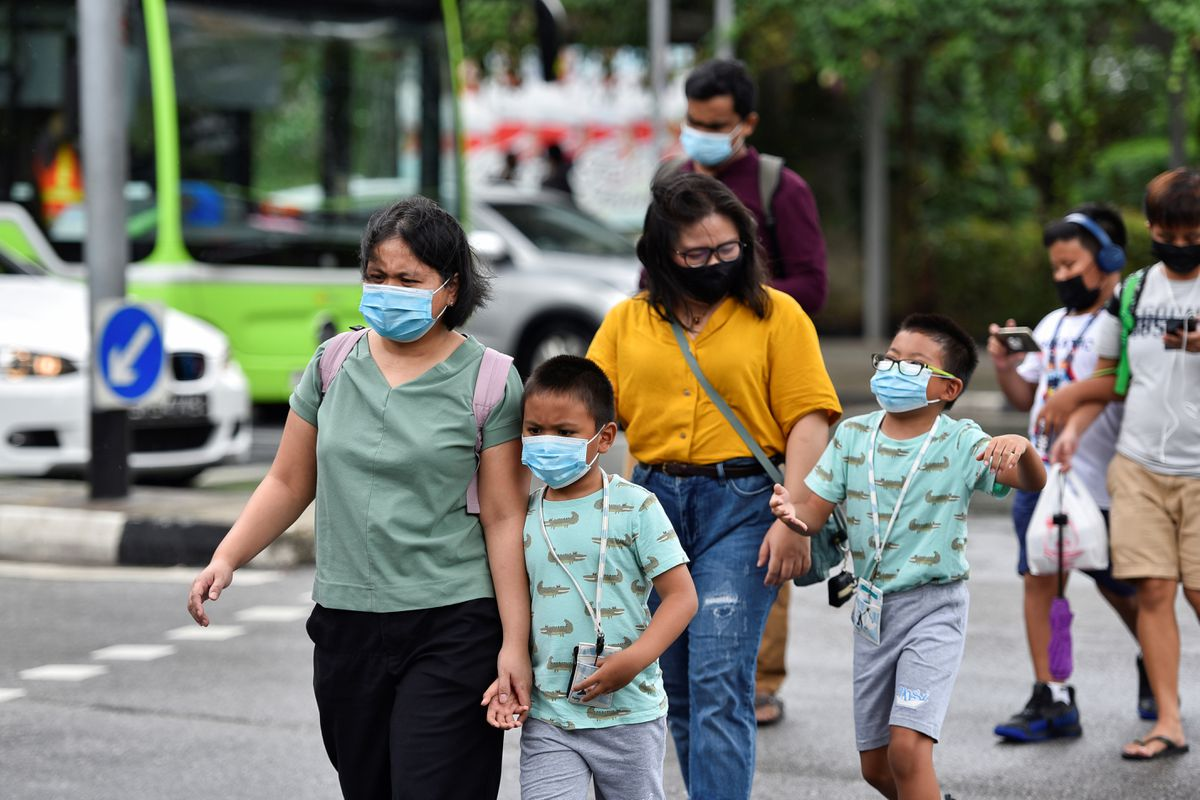 People wearing face masks cross a road amid the coronavirus disease outbreak in Singapore May 14, 2021. Photo by Reuters//Caroline Chia.