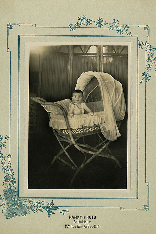 The Child in a Cradle was taken in around 1922, by a photo store named Namky-Photo in northern Bac Ninh Province.