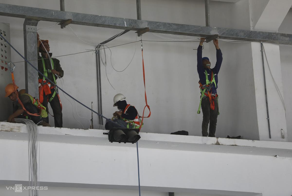 Công nhân lắp đặt hệ thống điện bên trong nhà máy.
