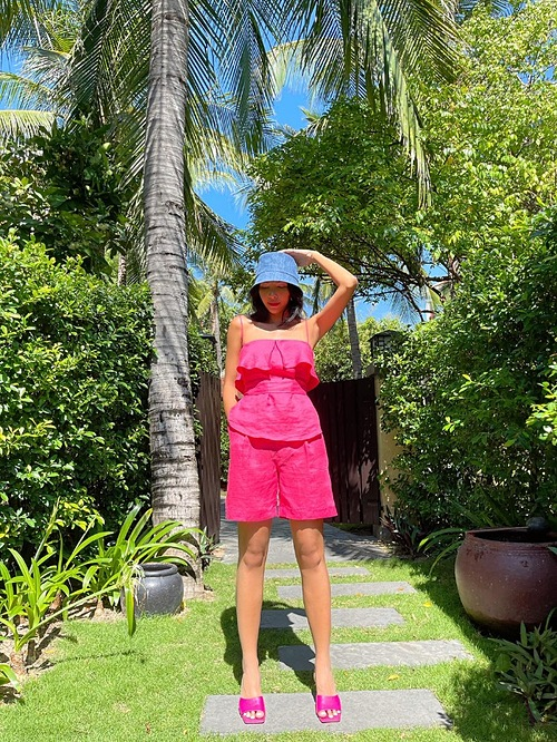 Model Minh Trieu also opts or a pink short, shirt and sandals. Embracing optimistic point of view for spring 2021, many designers have come up with a sea of outfits in bold, bright colors, from sunshine yellow to citrus orange and hot pink.