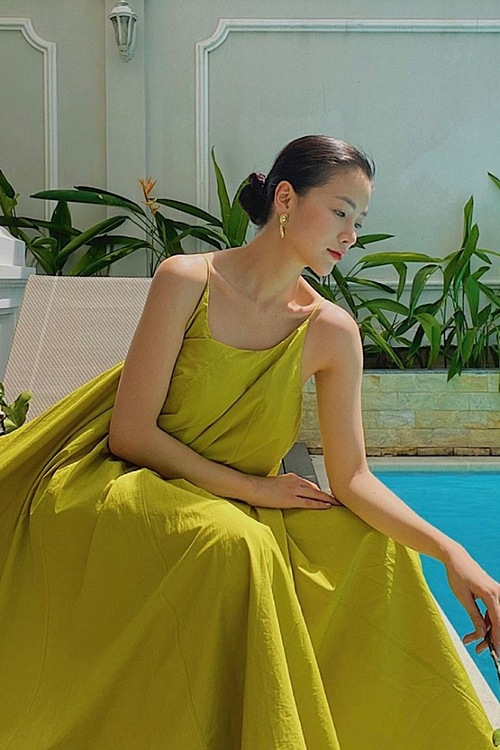 Model Phuong Khanh chooses a yellow relaxed dress while staying at home, reflecting the shade of summer days to come.