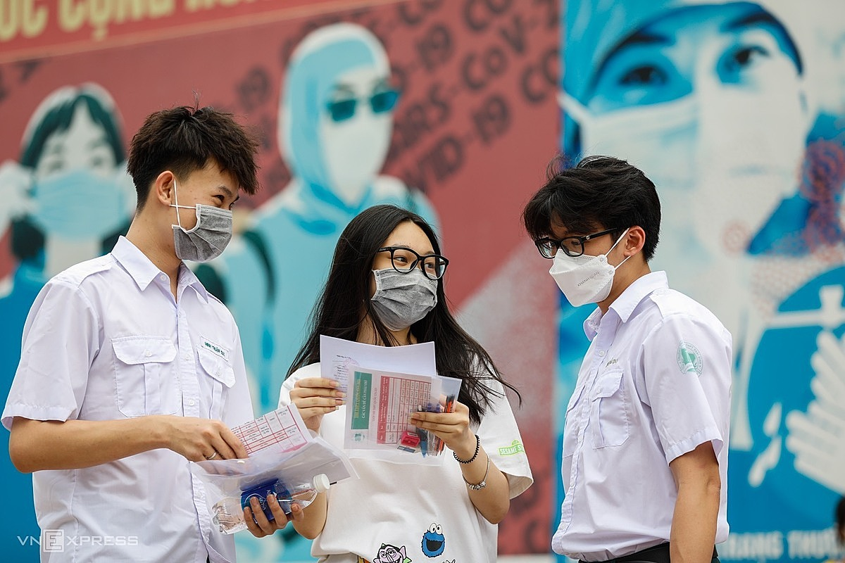 Saigon students talk after visiting their test site and completing the examination preparation procedures. Photo by VnExpress/Huu Khoa.