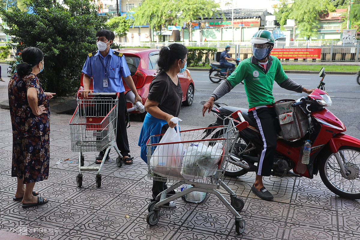 A shipper receives goods from his cusomer at a Co.op Mart supermarket branch on Truong Sa Street, July 11, 2021. Photo by VnExpress/Quynh Tran.