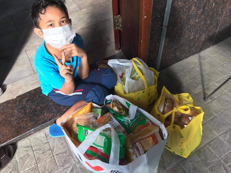 A family member of Moana Tranh, a Filipina living in District 9, poses for a photo next to the food package sent by CJ Van Burren. Photo courtesy of Moana Tranh.