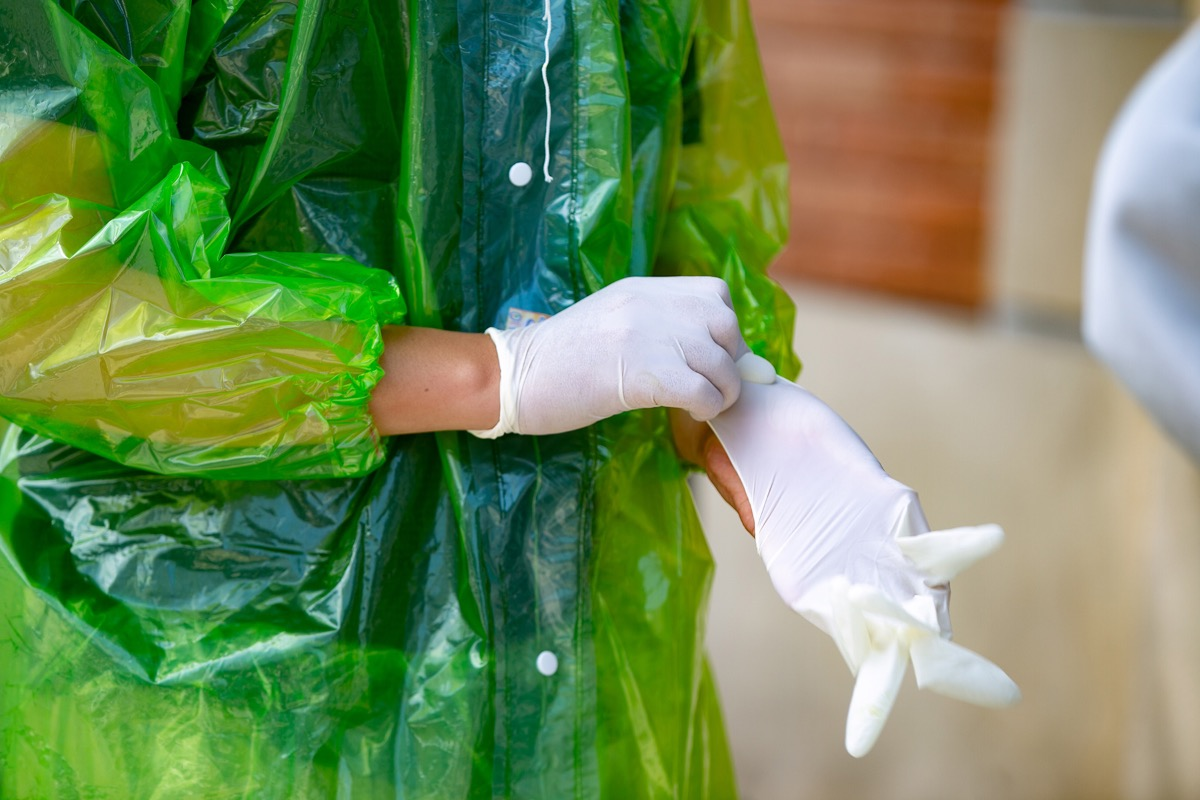 Without proper protective clothing, a man resorts to wearing a raincoat and surgical gloves.