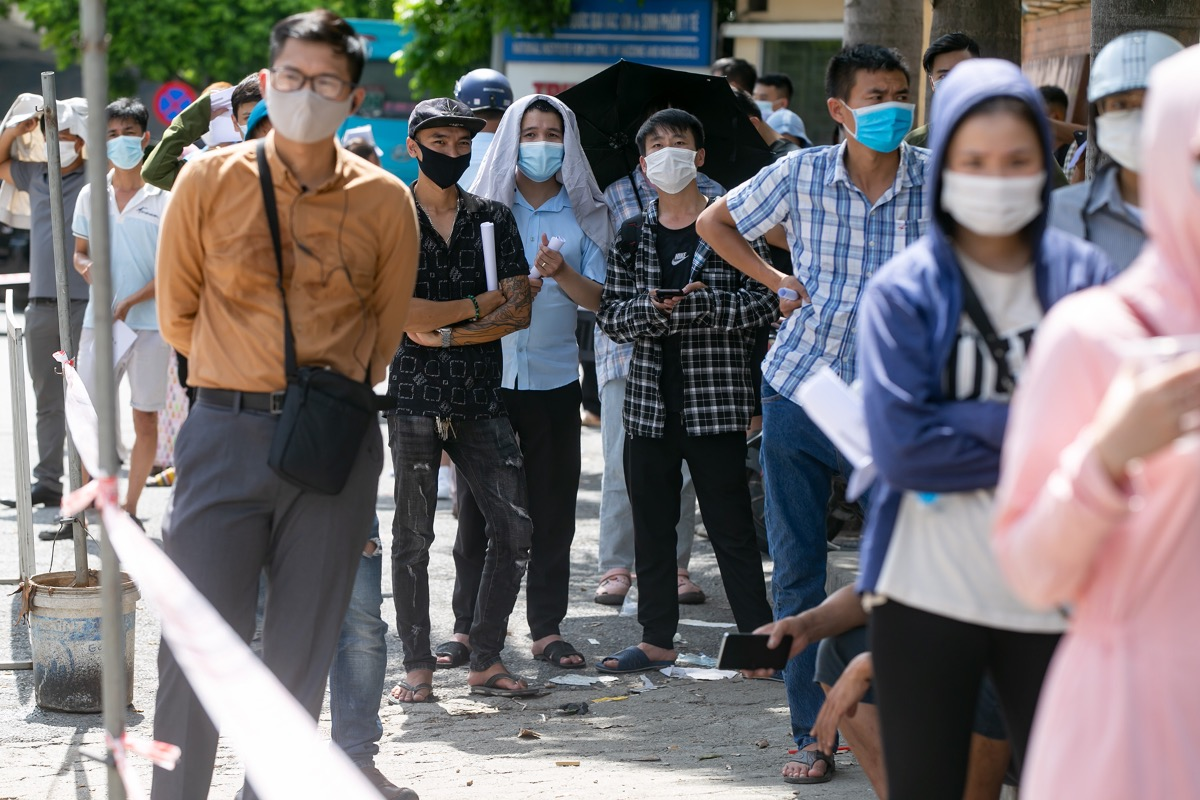 Hundreds of people wait for hours under the scorching sun, ignoring social distancing rules. Most are drivers and workers in industrial zones that require negative tests to recommence working.