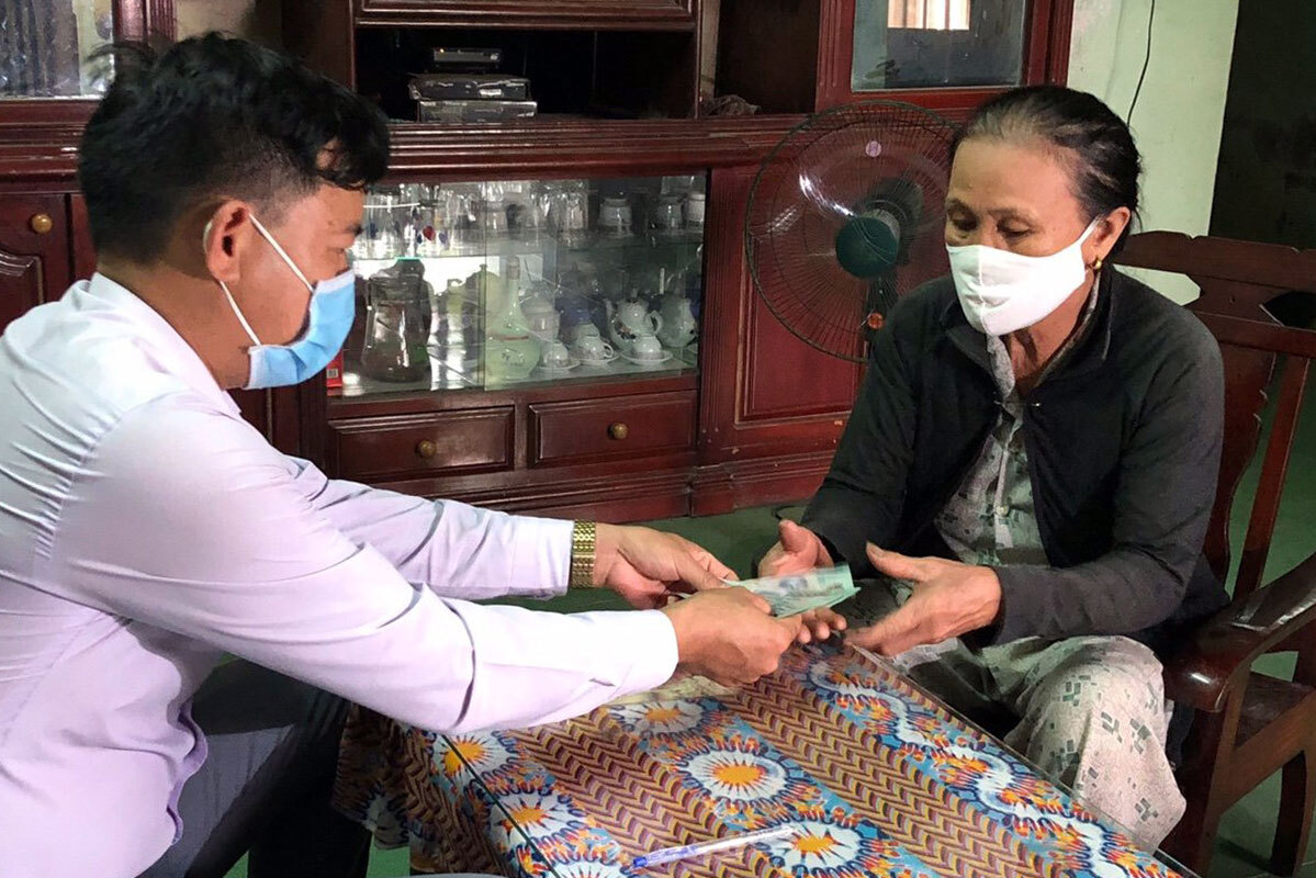 A women in Hoa Vang District receive money from the local authorities. Photo by VnExpress/Dong Hong.