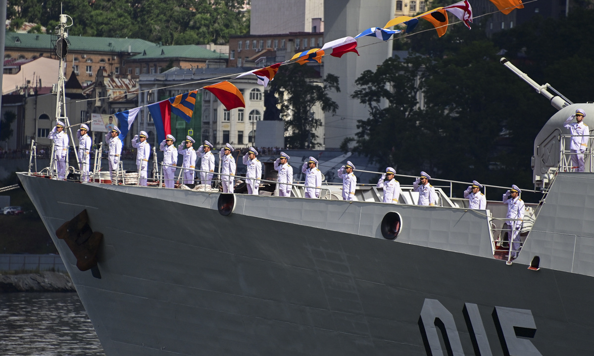 Vietnamese personnel on the 015 Tran Hung Dao frigate salute the command ship.