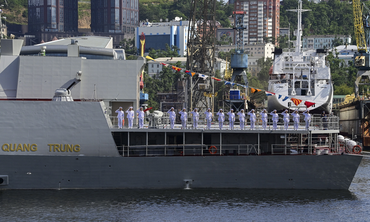 Personnel on the 016 Quang Trung frigate salute the command ship from the rear helipad.