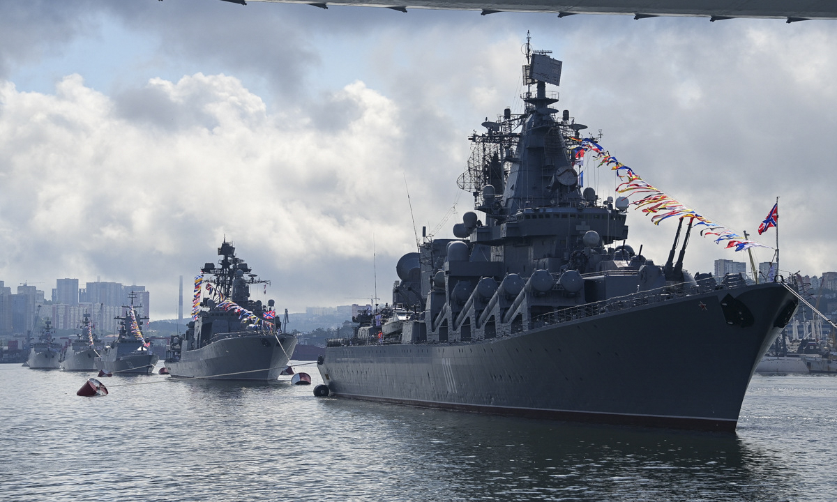 The Varyag cruiser, flagship of the Pacific Fleet, leads the parade.  The ship belongs to Russia's Project 1164 Atlant or Slava Class guided missile cruisers. She is 186 meters long, 21 meters wide and has a displacement of 12,000 tons. Varyags main armament is 16 P-500 Bazalt anti-ship missiles with a range of 550 kilometers (342 miles), 64 long-range air defense missiles, and 40 short-range air defense missiles.