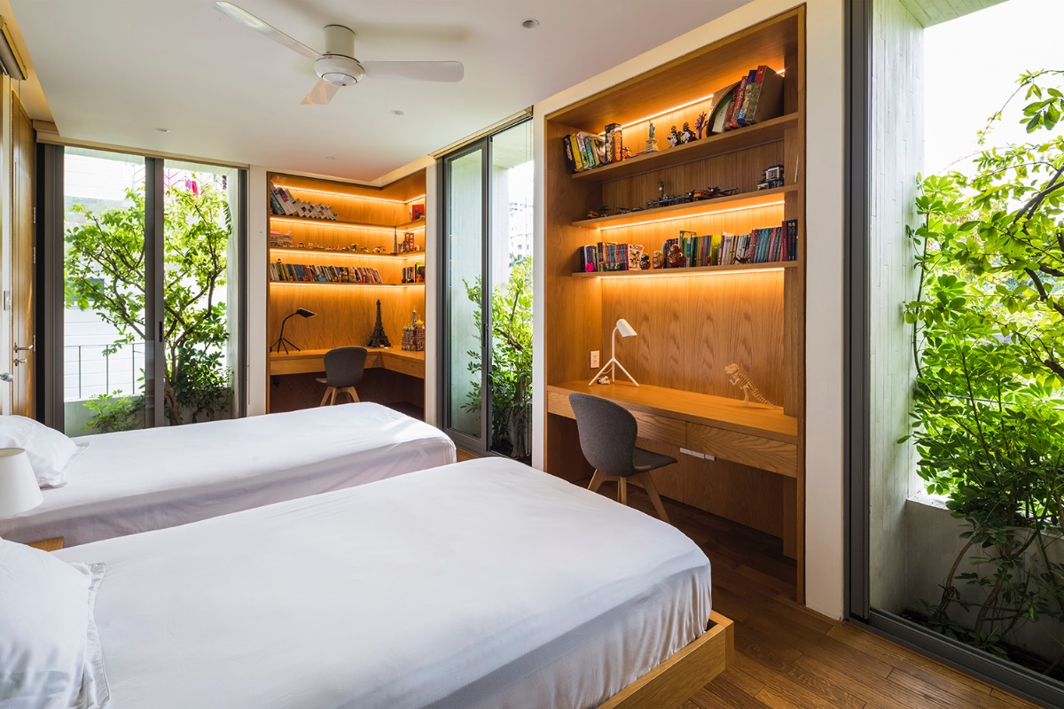 A bedroom on the second floor is given a warm touch with  greenery and wooden furniture.