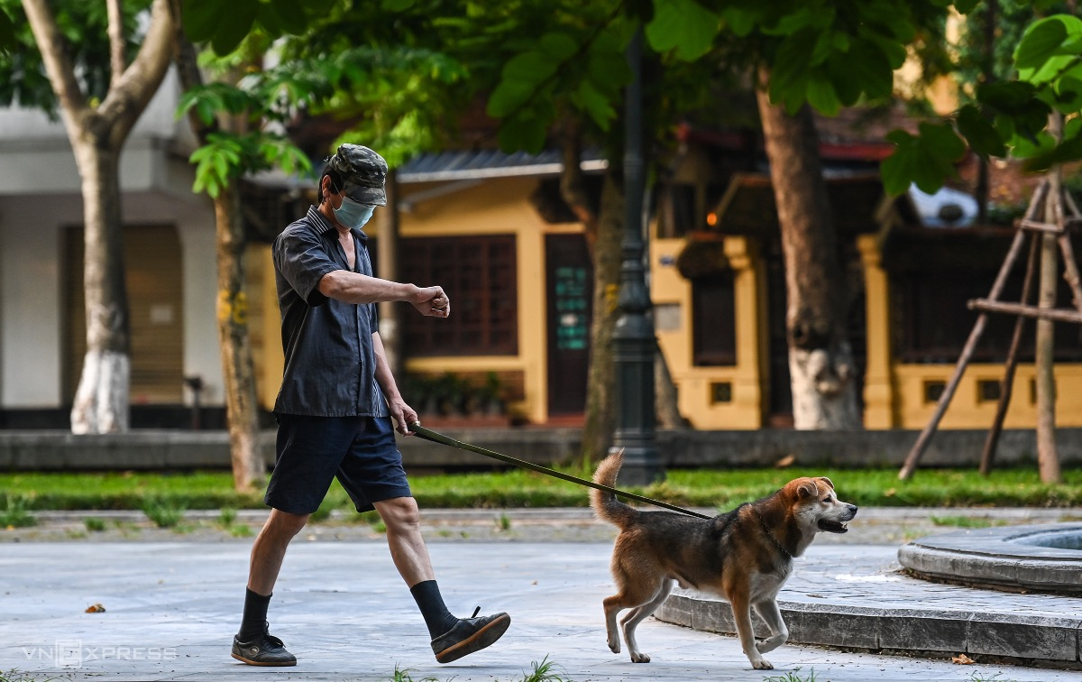 A man walks his dog in Hang Dau Park in violation of rules.