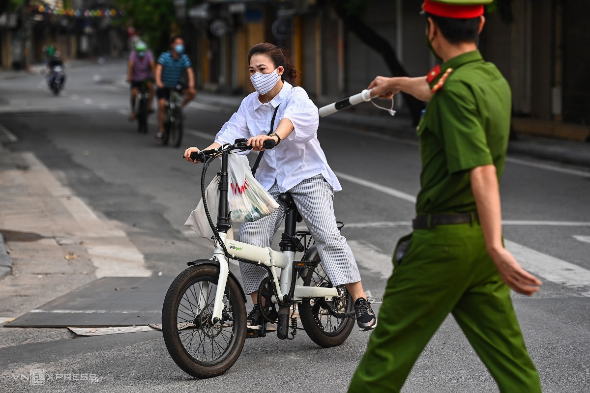 A woman is stopped by an officer on Luong Van Can Street.The 15-day lockdown is under Directive 16, which mandates the most stringent social distancing regulations like requiring people to stay at home and only go out for buying food or medicines or work at factories or businesses that are allowed to open.