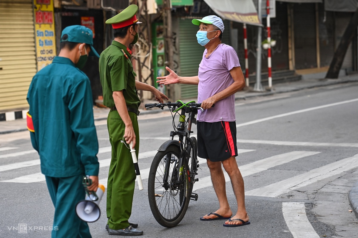 A man is stopped in Hoan Kiem District. Local authorities and police have set up a number of teams and checkpoints to confront violators. In the first three days of the lockdown 300 people and five organizations were fined for flouting rules.