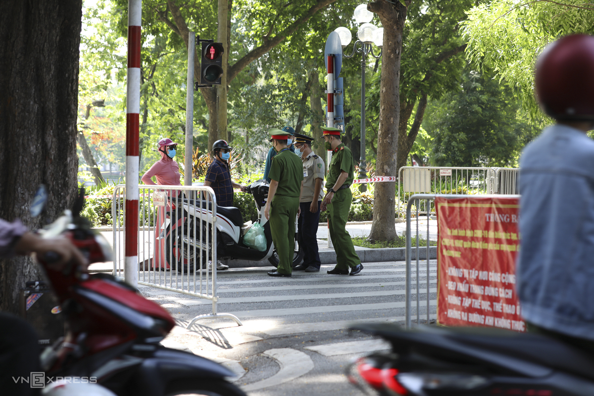 Police inspect commuters by Sword Lake in the heart of Hanoi. Three months into Vietnam's new Covid-19 community wave, the infection tally in the capital crossed 1,000 Tuesday night.