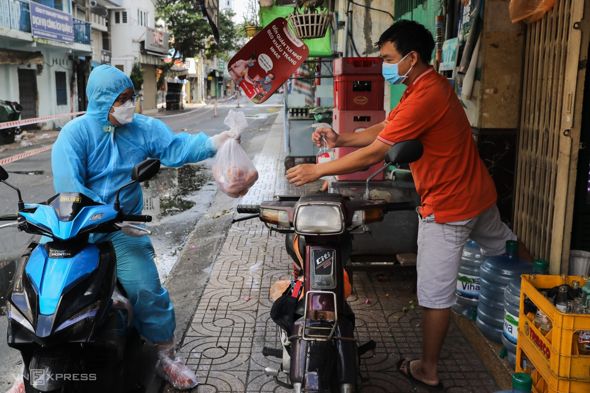 For those located further, volunteers use motorbikes to deliver goods. We have stayed at home for almost a month and still have enough groceries provided by the local authorities, said Tuong (left) while spraying alcohol onto a package of pork.