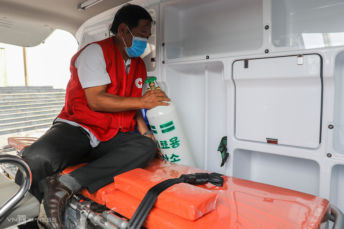 Minh, the van's driver, places an oxygen tank in its dedicated spot.