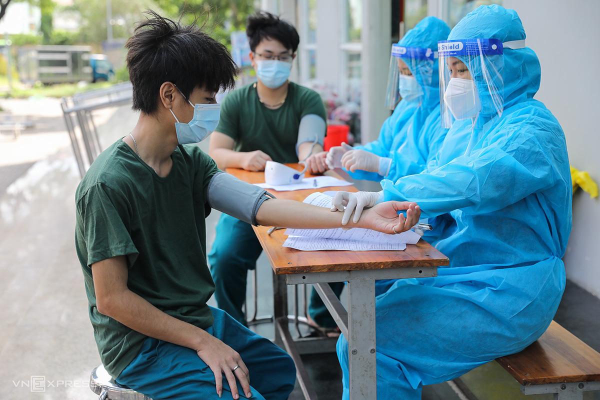 Two militiamen undergo health screening before getting injected.