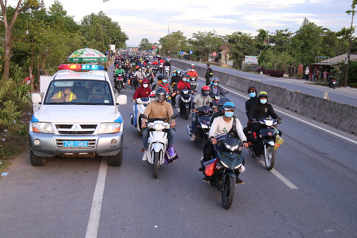 After passing through a Covid-19 check point in Thua Thien-Hue, a traffic police vehicle escorted a group of 700 people returning from HCMC and other southern localities on motorbikes to Quang Tri, another central province.
