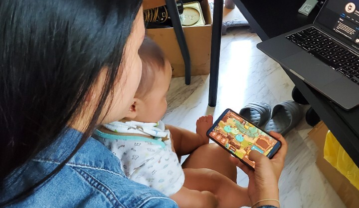 A woman plays Axie Infinity while holding a baby. Photo by Lorcan Gaming.