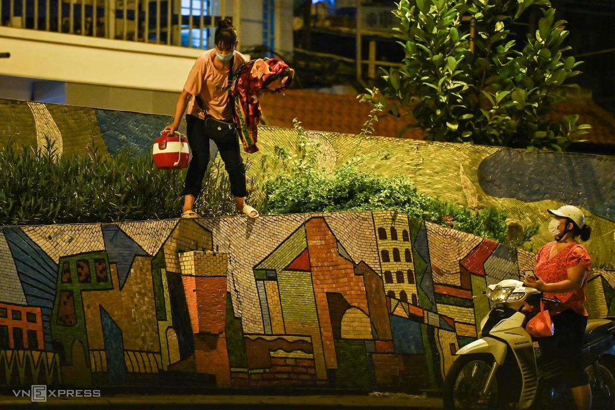 A woman climbs over the wall, bringing her personal stuff and getting out of the locked-down area.