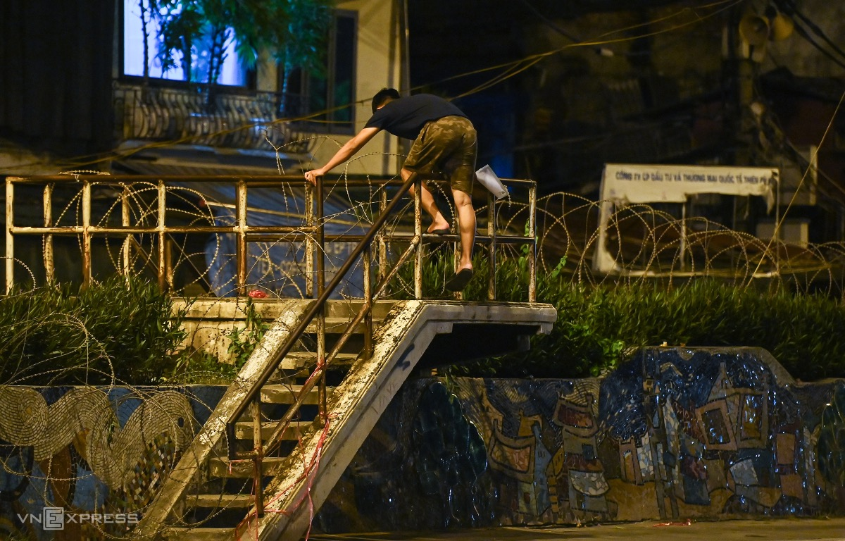 Many people climb over the barbed wire fence to get out of the locked-down area.