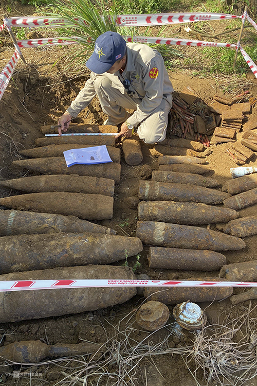 A staff measures the bomb at the disposal site in Quang Tri Provice, August 2, 2021. Photo by VnExpres/Quang Ha