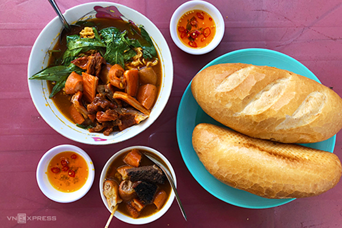 A loaf of banh mi accompanied with a stew made of beef and pork entrails called pha lau (Offal stew) is not a bad idea for Saigonese as the dish originated from China and was imported to Saigon 100 years ago and chefs add local taste to suit Vietnamese foodies. Diners can drop Ms.Oanhs tall inside Xom Chieu Market in District 4, recommended by food bloggers.  The main ingredient of the pha lau in this eatery is beef offal – liver, stomach and tripe. On collecting an order, the owner starts to cut the offal into bite-sized chunks. Then she puts them in a bowl then adds fragrant, dense broth rendered richer with coconut milk. The long-shimmered beef offal is tender, juicy and crunchy. Adding to the enjoyment of the dish is the sweet and sour taste of fish sauce with some kumquat juice. Eaters can tell the owner if they want their sauce spicy or not.The shop at 200/48 Xom Chieu, District 4 has been in operation for 20 years and opens from 5 p.m. to 10 p.m. The average price for one serving is VND25,000 ($1.08).