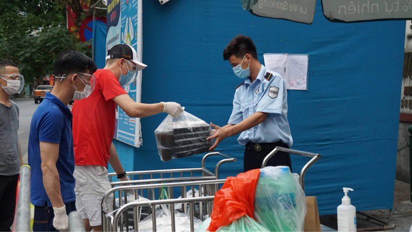 The restaurants staff deliver servings of rice to a security officer of the Hanoi Lung Hospital, July 2021. Photo courtesy of Dinh Thanh Tung.