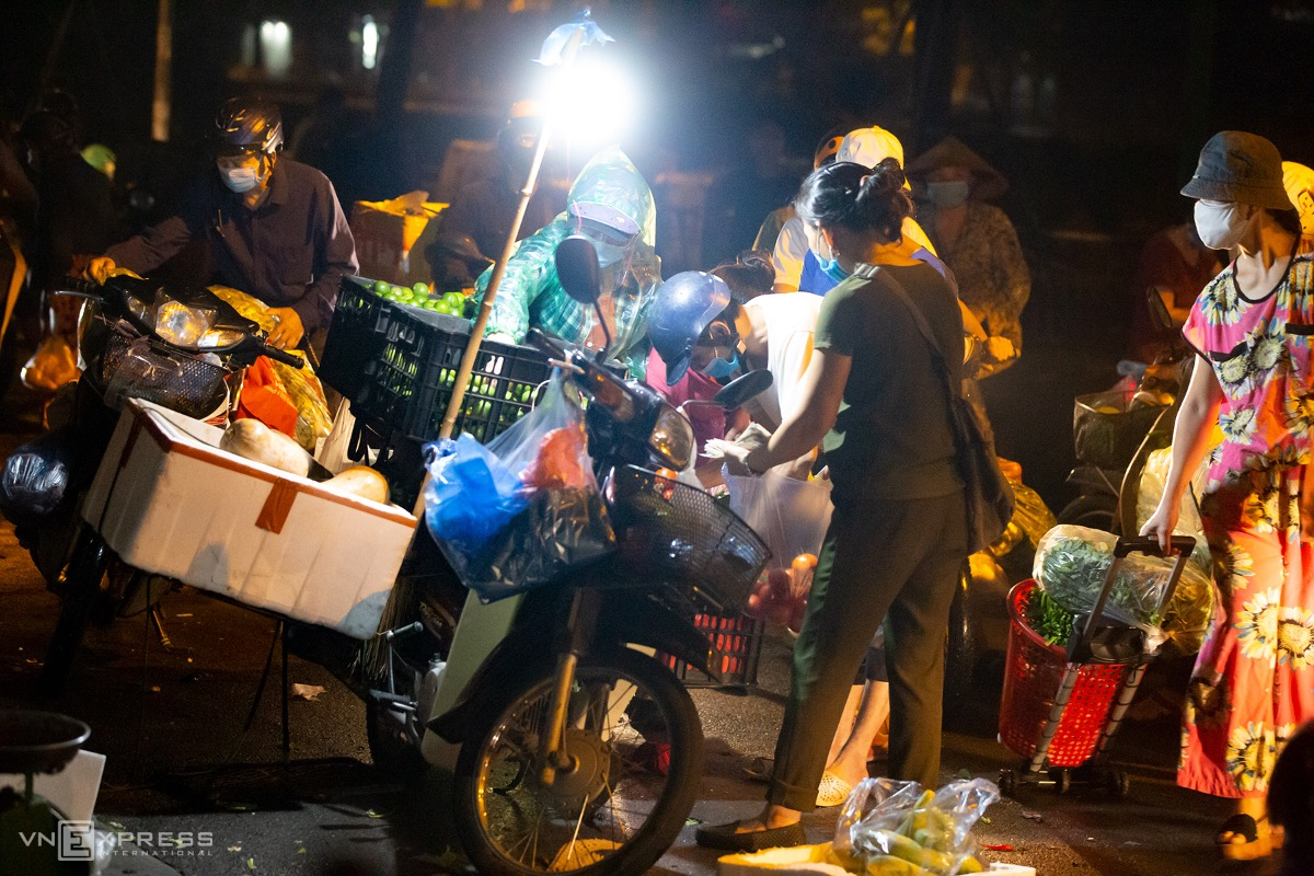 People go to the market before dawn to avoid Covid checkpoints and local authorities, who will ask them for shopping vouchers or approval documents if they want to venture out.