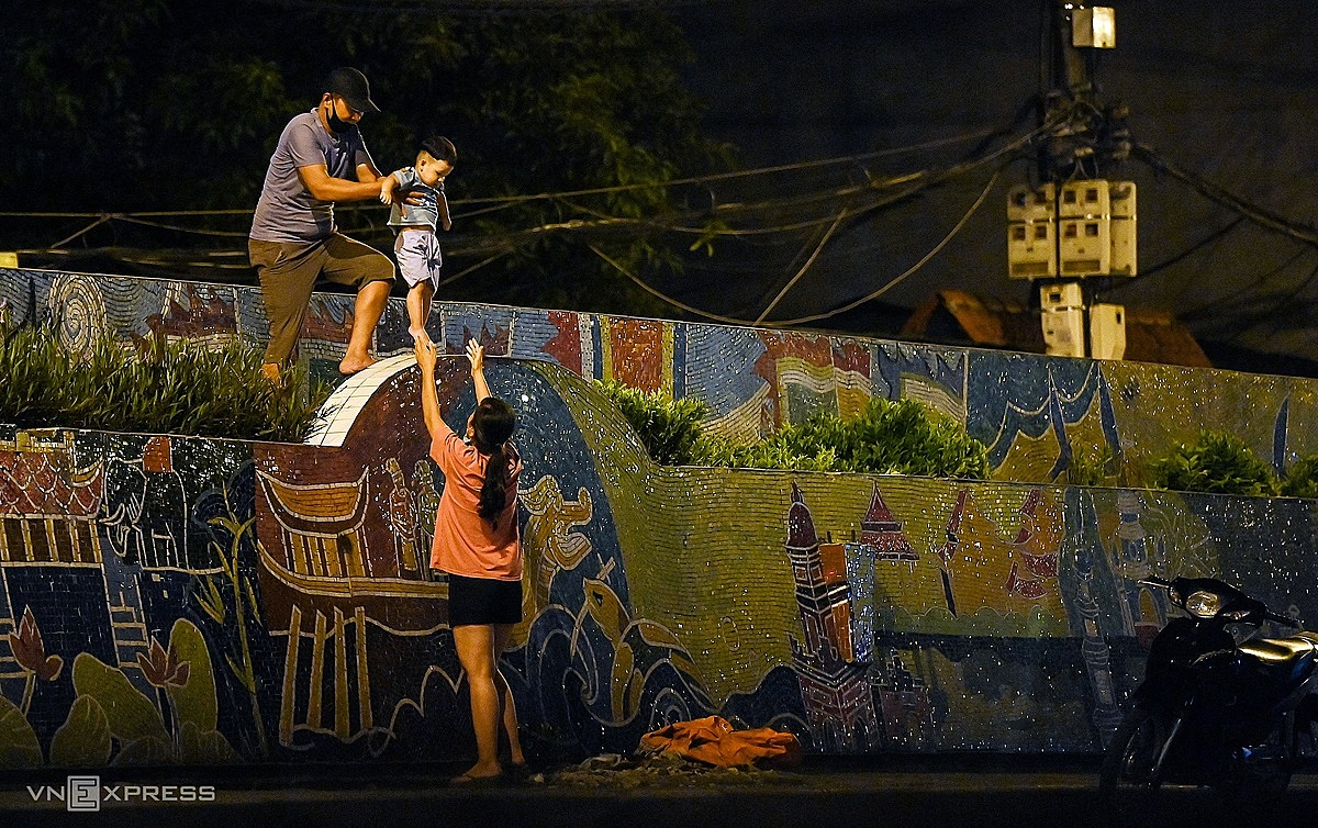 A family leaves a locked-down area in Hanois Hoan Kiem District in the middle of the night, August, 2021. Photo by VnExpress/Giang Huy.