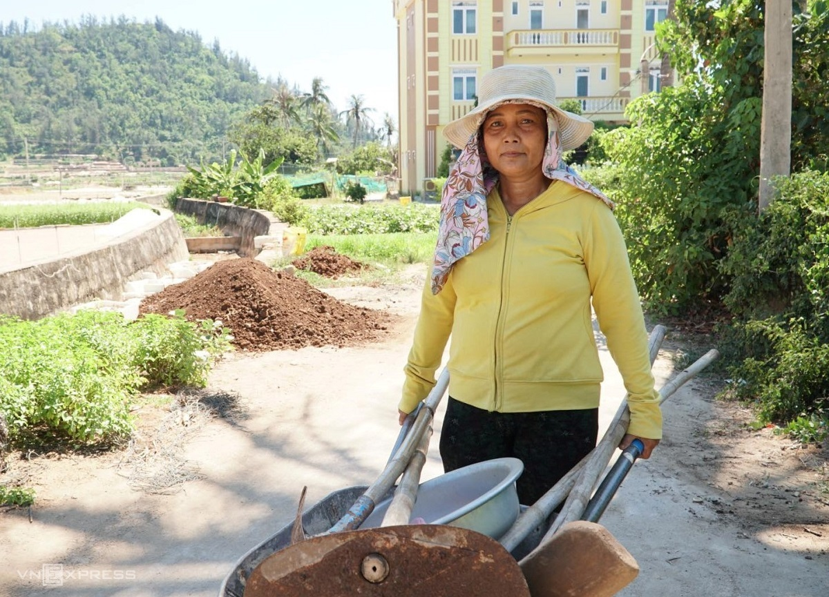 Tran Thi Cuong, a hotel owner in Ly Son Island, pushes a wheelbarrow back from her onion farm. Photo by Chau Dai Duong
