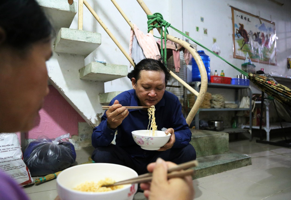 Huynh Van Son and his wife eats instant noodles back at their rented room inn in Binh Tan District, HCMC, after their failed trip to their hometown on August 15, 2021. Photo by VnExpress/Dinh Van