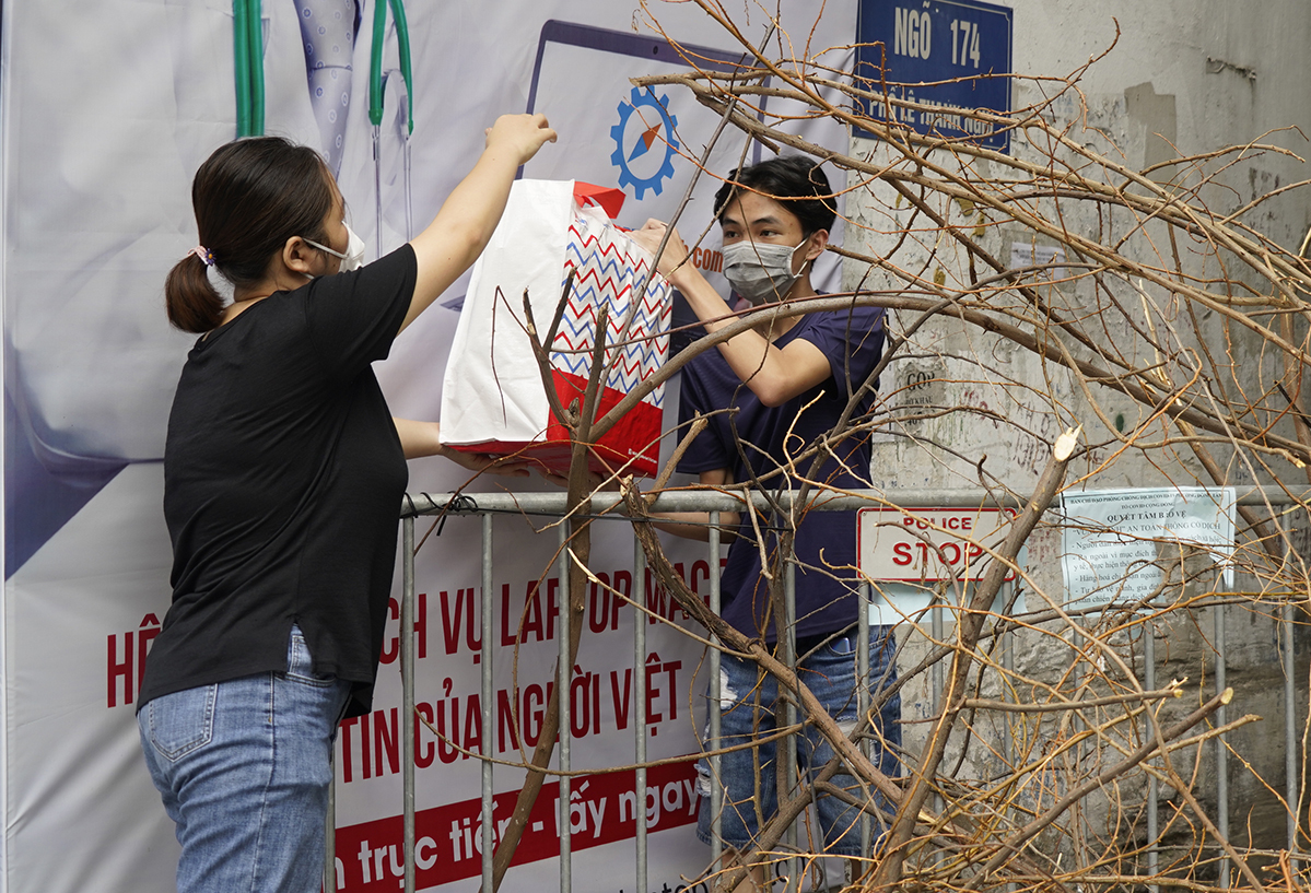 A student of Hanoi Hanoi University of Science and Technology receives food from a teacher while being stranded in a lockdown alley on Le Thanh Nghi Street. Photo courtesy of Hanoi University of Science and Technology.